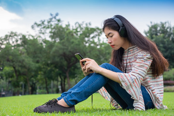 Asian young girl stands listening to music from a smartphone using headphones and copy space. At public park the city center happy and relax On his vacation. she is 25-30 years old.