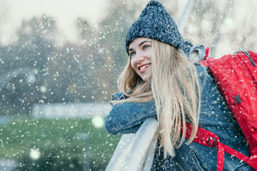 young blonde happy woman tourist smiling watching snowfall. Winter holiday, youth, christmas, vacation, adventure, concept