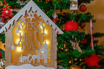 Wooden crib design with Merry Christmas message before lit tree. A wood carved illuminated crib with a winter scene against a decorated artificial Christmas tree background.