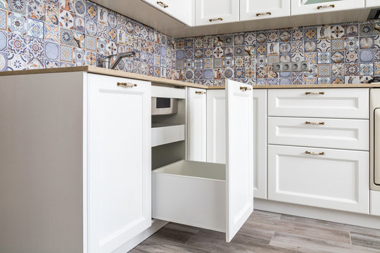Opened drawer with high front under a sink, large drawer for a garbage bin, inner drawer for garbage bags storage and small detergents. Clever solution for kitchen storage and organization.