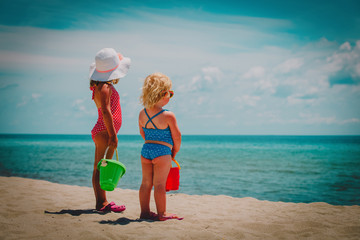 little girls play with sand on summer beach