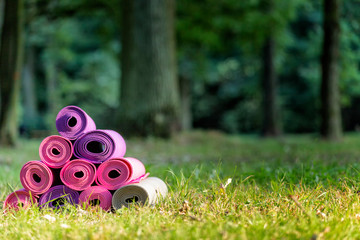 joga matts stacked on the green grass, springtime in public park