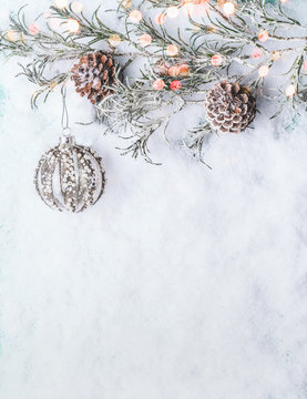 Christmas background  with vintage bauble , frozen branches and cones on snow with bokeh, top view with copy space for your design, border