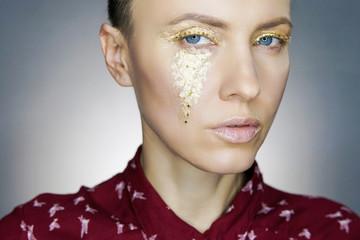 Beautiful woman with golden makeup over dark background