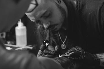Tattooist making a tattoo in studio