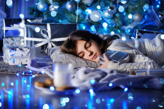 Girl  sleeping under the christma tree waiting for presents