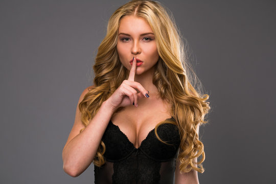 Young beautiful woman has put forefinger to lips as sign of silence