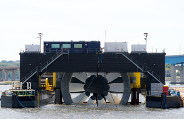 Giant tidal turbine docked in a harbor. It is held in a ship designed to hold and transport it. Sky is overcast. Walkways on ship give sense of scale. Identifying marks removed. Room for text. Wall mural