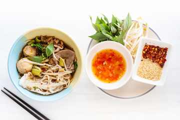 Spicy rice noodles soup in a bowl with chopsticks and ingredients, Asian food