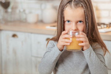 little girl drinking juice from glass. healthy child diet and vitamin nutrition