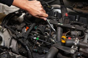 Mechanic repairs cars in his workshop using various tools