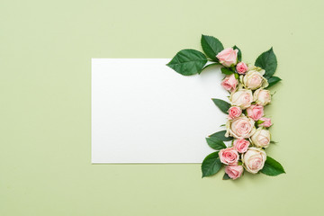 empty white paper card with bunch of roses on green background. holiday invitation mockup