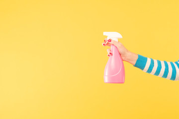 female hand holding bright pink cleanser sprayer on yellow background. cleaning housework and household chores