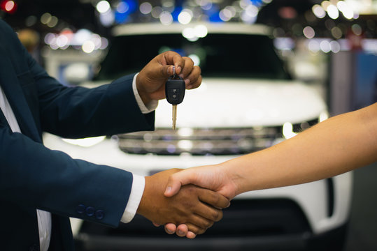 Handshake of two businessmen when selling a car in a motor show, auto business, car sale, deal, gesture and people concept - close up of dealer giving key to new owner and shaking hands in showroom.