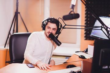 Portrait of radio host using sound mixer on table in studio.