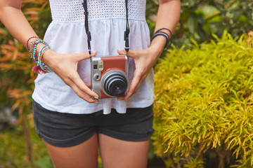 Girl posing with retro vintage camera outdoors.