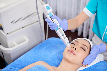 From above shot of master in gloves doing face treatment procedure with electronic instrument