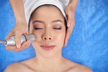 From above shot of young Asian woman with makeup enjoying facial spa treatment in salon