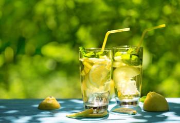 Two glasses of homemade lemonade on table on the street