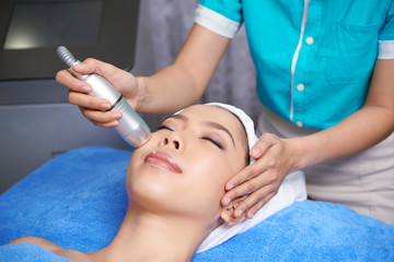 Young Asian woman lying on soft towel having face treatment procedure in spa salon