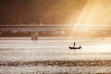 Fishing under the bridge in the morning sun at Lake Kawaguchi, one of the scenic Five Lakes in the northern foothills of Mount Fuji, Japan.