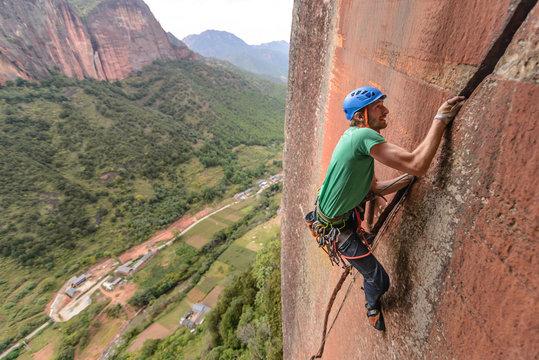 Rock climber scaling rock face, Liming, Yunnan, China
