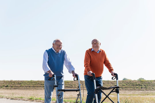Two old friends walking on a country road, using wheeled walkers
