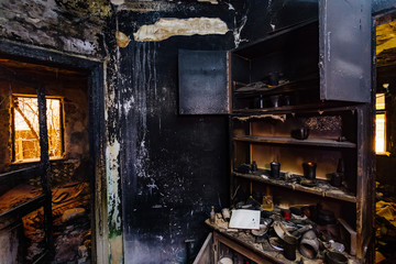 Burnt house interior. Burned furniture, kitchen cabinet, charred walls and ceiling in black soot