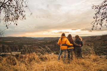 Spain, Alquezar, three friends embracing on a hill overlooking the scenery