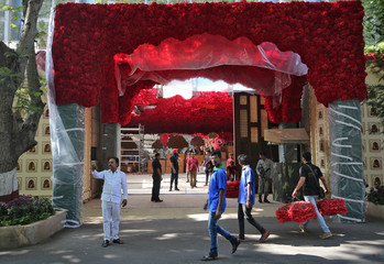 A man carries bunches of artificial flowers to decorate Antilia, the house of the Chairman of Reliance Industries Mukesh Ambani, ahead of his daughter's wedding, in Mumbai