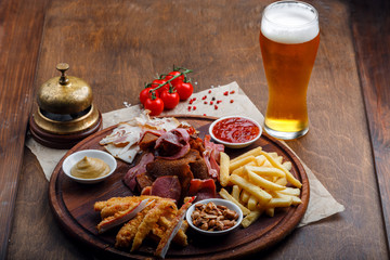 Big set of snacks for beer or alcohol and it includes smoked pork meat, french fries, fried bread, crab sticks and nuts