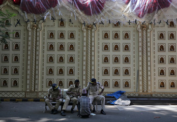Policemen sit in front of a decorated wall of Antilia, the house of the Chairman of Reliance Industries Mukesh Ambani, ahead of Mukesh's daughter wedding, in Mumbai