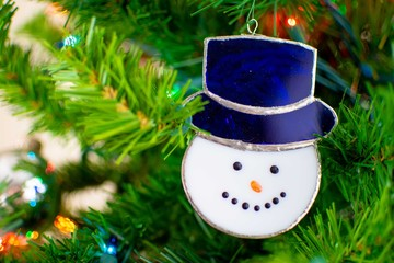 A glass snowman ornament hangs on a Christmas Tree