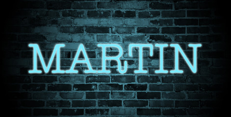 first name Martin in blue neon on brick wall
