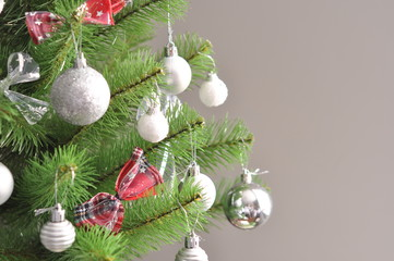 photo of decorated christmas tree. shiny balls, gray ornaments, bows on green branches. New year photo. Use for background, invitation, greeting card.