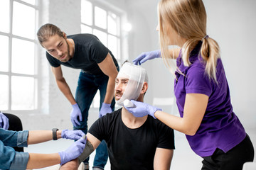 Group of young people during the first aid training with instructor showing how to tie a bandage on the head of injured person