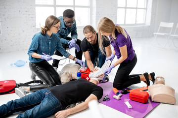 Group of young people during the first aid training with instructor showing how to apply a bandage on injured person