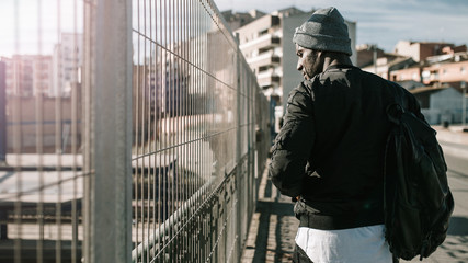 Young african american man walking by the city in a sunny day