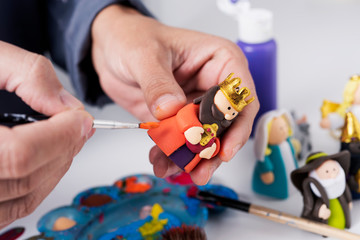 man painting a maggi of a nativity scene