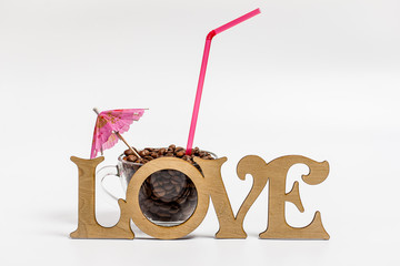 Glass cup with fragrant coffee beans with a straw and an umbrella on a white background and the words love