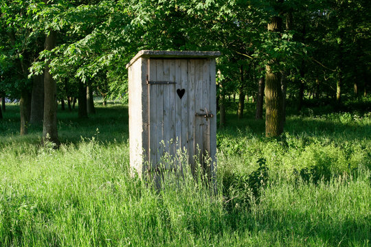 Old fashioned toilet building with wooden door standing outside among the grass with trees in the background.