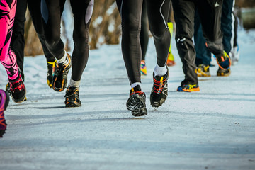 Fototapete - legs group of runners running on winter trail road in snow