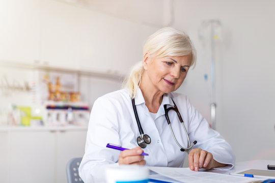 Senior female doctor writing a prescription in her office