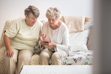 Two senior woman learning together how to use a mobile phone