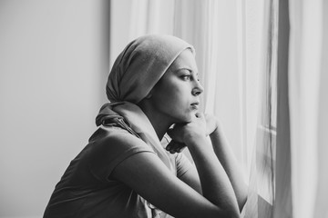 Black and white photo of thoughtful young girl suffering from ovarian cancer wearing headscarf and looking through the window in medical center