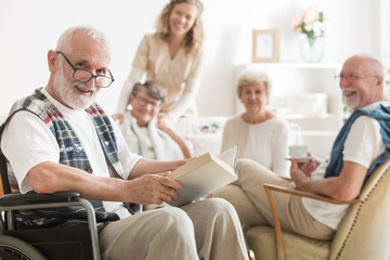 Old man with glasses sitting on wheelchair reading a book