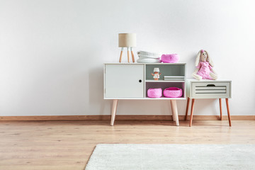 White and pink decor in scandinavian baby playroom interior, copy space on empty wall