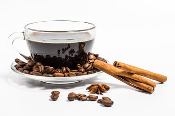 Glass cup with coffee, cinnamon sticks and grains on a white background