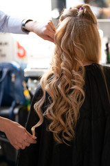 Foto op Aluminium Kapsalon beautiful adult blonde client sits in a chair while a hairdresser master in the salon does her hair with a corrugation and a Perm