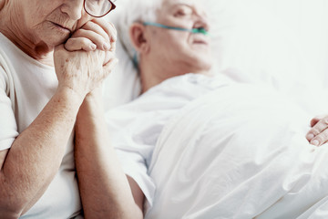 Sad senior woman holding hand of her cancer sick husband lying in hospice bed, photo with copy space